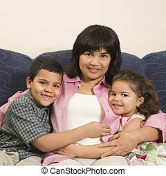 Family hugging together. - Family sitting on couch hugging...