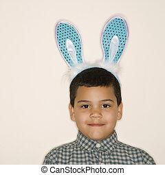 Boy wearing bunny ears. - Portrait of Hispanic boy wearing...