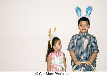 Kids wearing bunny ears. - Hispanic girl looking up at...