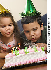 Kids having birthday party - Hispanic girl and boy wearing...