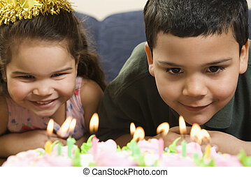 Kids and birthday cake. - Hispanic girl and boy leaning in...
