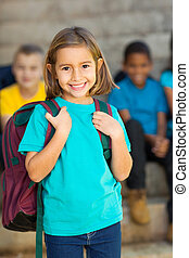 cute elementary schoolgirl carrying schoolbag in front of...
