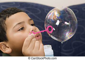 Boy blowing bubble - Hispanic boy blowing large soap bubble...