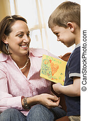 Boy giving mom drawing - Caucasian boy giving mid adult...