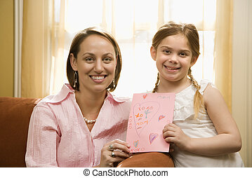Girl giving mom drawing - Caucasian girl giving mid adult...