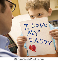 Boy giving dad drawing - Caucasian boy giving mid adult...