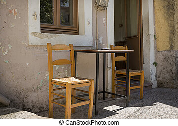 Table and chairs in front of a cafenion in Greece