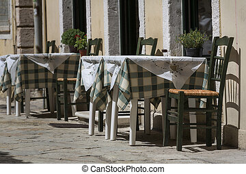 Table and chairs in front of a restaurant in Greece