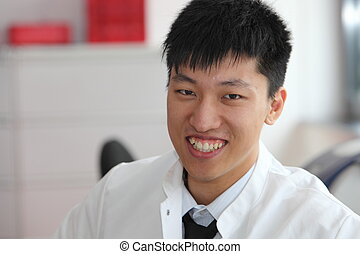 Smiling Asian man in a lab coat - Head and shoulders...