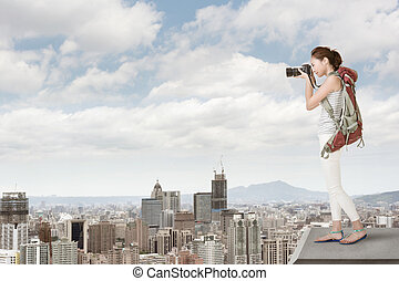 photographing - Asian young woman with professional camera...