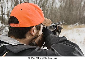 Man aiming shotgun. - Caucasian male aiming shotgun out...