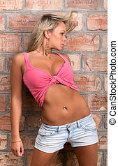 glamorous girl in a pink shirt with a naked belly against a...