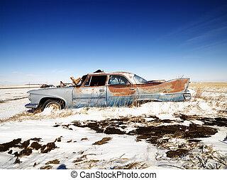 Rusted classic car. - Classic rusted car in snowy junkyard.