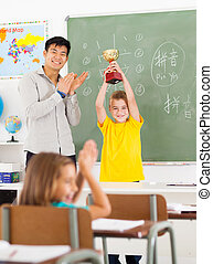 male teacher applauding for student - cheerful male Chinese...