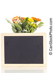 Bunch of flowers with blank blackboard