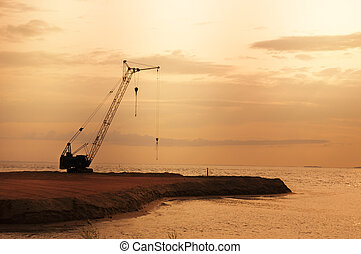 Building crane on the beach at suns