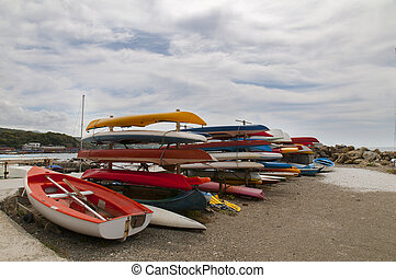 lots of colorful kayaks on the beach