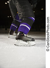 Ice hockey player - Low angle of hockey players legs and...