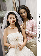 Bride and friend admiring dress - Asian bride and...