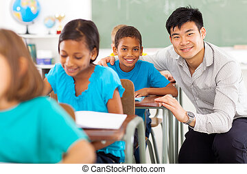 primary teacher helping student in classroom - portrait of...