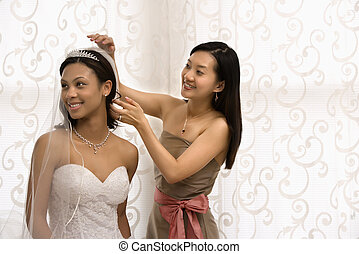 Bride and bridesmaid portrait - Asian bridesmaid adjusting...