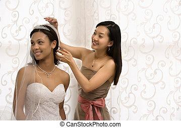 Bride and bridesmaid portrait. - Asian bridesmaid adjusting...
