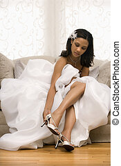 Bridal portrait - African-American bride placing shoe on...