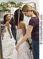 Seamstress measuring bride. - Caucasian seamstress measuring...