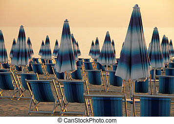 beach at sunset - scene with closed blue and white striped...