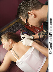 Woman getting tattoo - Caucasian male tattoo artist...