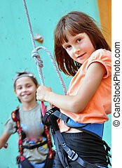children with climbing equipment against the training wall -...