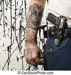 Man with gun - Caucasian tattooed man wearing holster with...