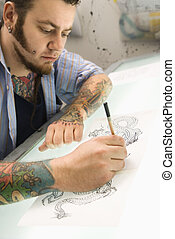 Man drawing tattoo - Caucasian male tattoo artist drawing...
