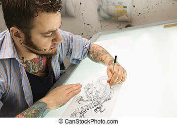Tattoo artist - Caucasian male tattoo artist drawing tattoo...