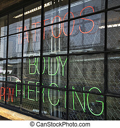 Tattoo shop sign. - Neon sign in window for tattoos and body...