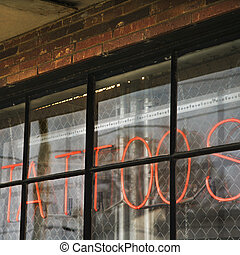 Tattoo neon sign. - Neon sign in window for tattoos and body...