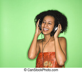 Woman listening to music - African-American woman listening...