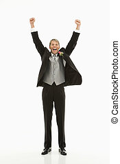 Groom in tuxedo. - Caucasian groom with arms raised in air.