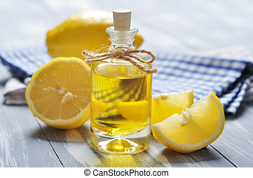 lemon oil in a glass bottle with fresh wooden background...