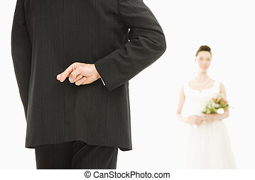 Groom with crossed fingers. - Back of groom with his fingers...