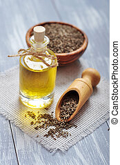 cumin oil in a glass bottle with cumin seeds on wooden...