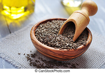 Cumin seeds in a wooden plate on wooden background