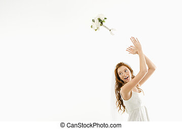 Bride tossing bouquet - Portrait of Caucasian bride tossing...