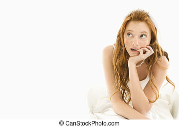 Bride biting her finger - Portrait of sitting Caucasian...