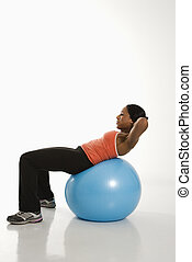 Woman exercising with ball - Side view of African American...