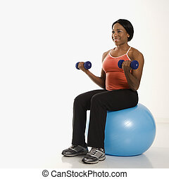 Woman lifting weights on ball.