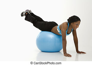 Woman exercising with ball - African American young adult...