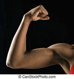 Strong female bicep flexing. - Arm of African American woman...
