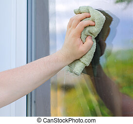 Male hand with rag washing window outdoors