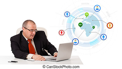 businessman sitting at desk and looking laptop with globe...